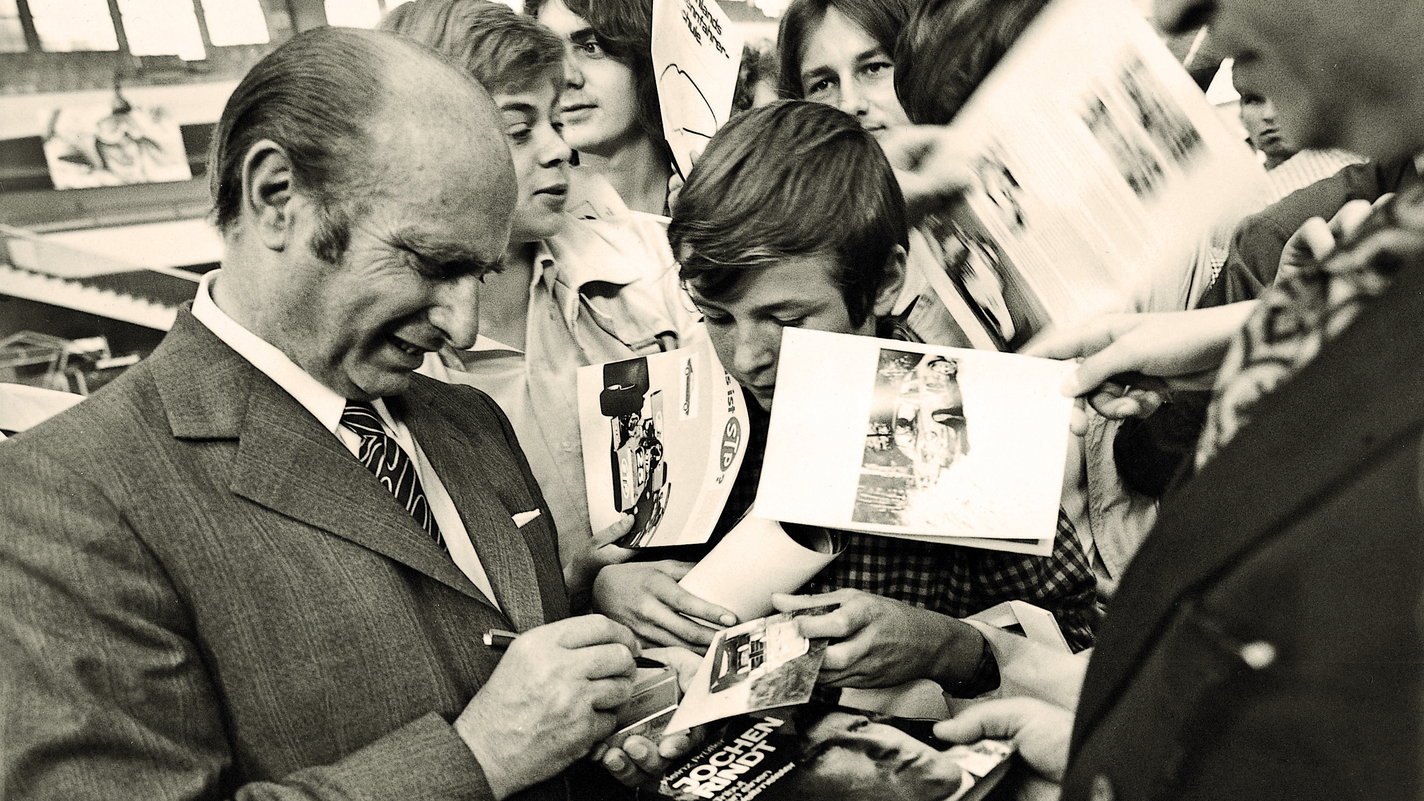 Juan Manuel Fangio, five-time Formula 1 World Champion, signs autographs for his fans